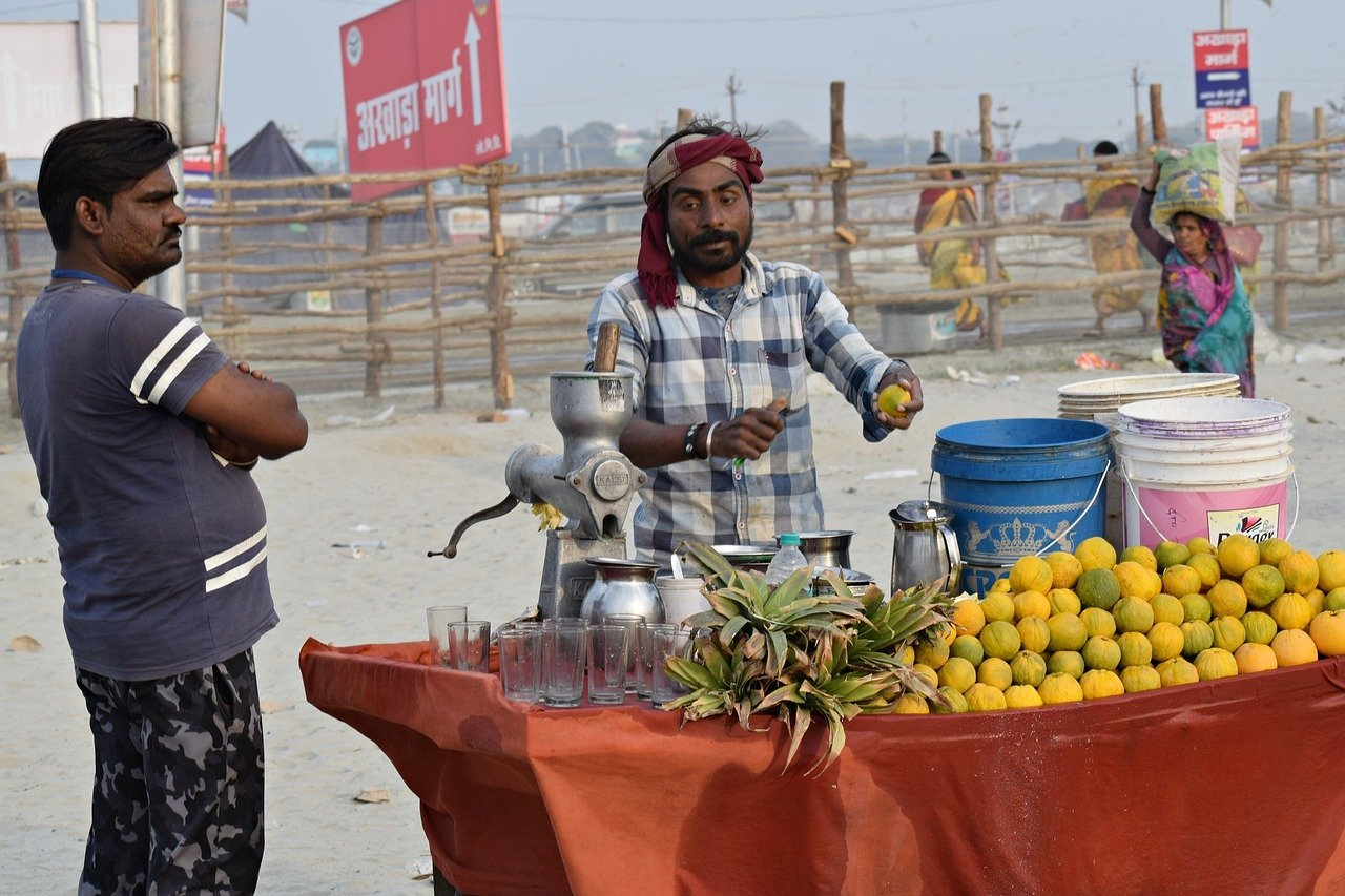 two men standing at a fresh fruit stand in India